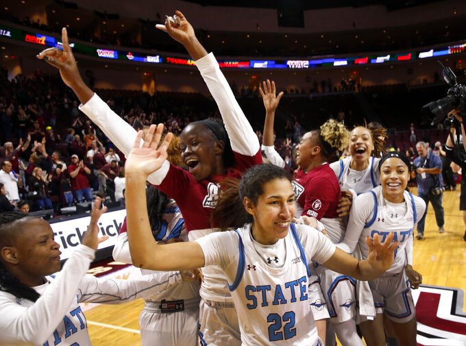 New Mexico State players celebrate after defeating Texas-Rio Grande Valley 76-73 in double overtime during a NCAA college basketball Western Athletic Conference Women's Tournament championship game Saturday, March 16, 2019, in Las Vegas. New Mexico State guard Kalei Atkinson (22) is at center. (AP Photo/Steve Marcus)