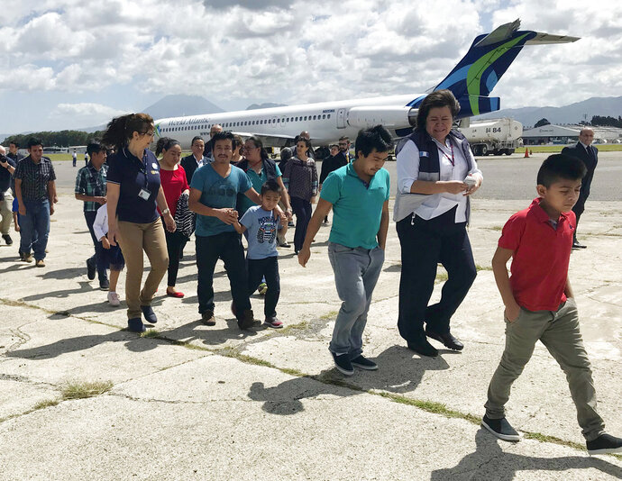 Families separated under President Donald Trump administration's zero tolerance policy return home to Guatemala City, Guatemala, Tuesday, July 10, 2018, after being deported from the United States. After lining up on the tarmac, they headed to a processing center where they were screened and given identification before being released back into the country.  (AP Photo/Colleen Long)