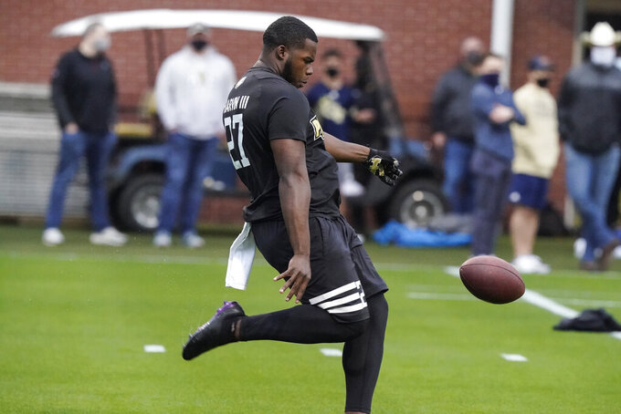 FILE - In this March 16, 2021, file photo, Georgia Tech punter Pressley Harvin III punts the ball  during the school's Pro Day football workout for NFL scouts in Atlanta.  NFL scouts who gathered for Georgia Tech's pro day didn't just want to see 263-pound punter Pressley Harvin boot the ball a mile. They also asked him to throw some passes, and he dazzled them with his arm, too. (AP Photo/Brynn Anderson, File)