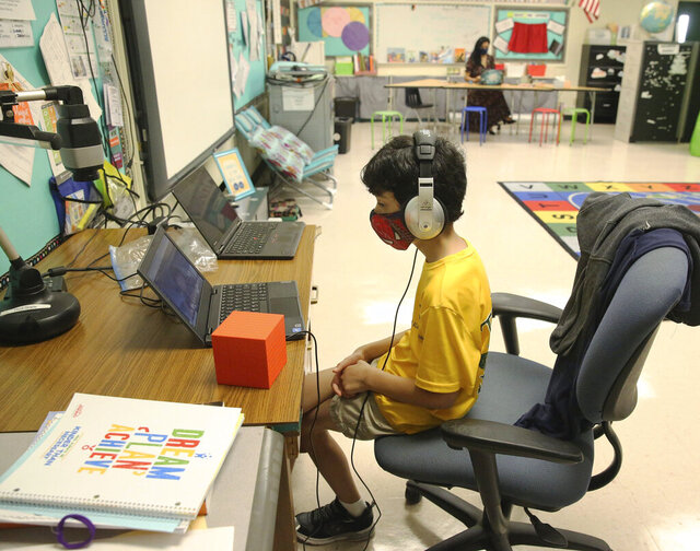 FILE - In this Wednesday, Aug. 19, 2020 file photo, Nova Blanche Forman Elementary School teacher Attiya Batool, teaches her 4th grade class virtually as her son, Nabeel, does his second grade classwork online wearing a face mask and headphones during the first day of school in Broward, in Davie, Fla. This year, many families are dealing with a first: building their back-to-school shopping plans around distance learning. As the COVID-19 pandemic leads students to take on instruction at home rather than in the classroom, consumers expect to spend more on back-to-school purchases in 2020 than last year.  (Emily Michot/Miami Herald via AP, File)