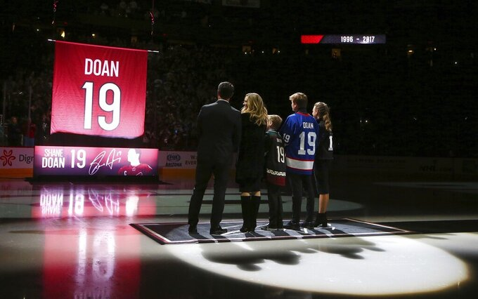 FILE - In this Feb. 24, 2019 file photo, from left to right Shane Doan, left, wife Andrea Doan, children Carson Doan, Josh Doan, and Karys Doan, watch as the Arizona Coyotes retire Shane's jersey during a ceremony prior to an NHL hockey game against the Winnipeg Jets in Glendale, Ariz.  The Coyotes picked Shane Doan's son Josh with the 37th pick in the NHL draft, Saturday, July 24, 2021.  (AP Photo/Ross D. Franklin, File)