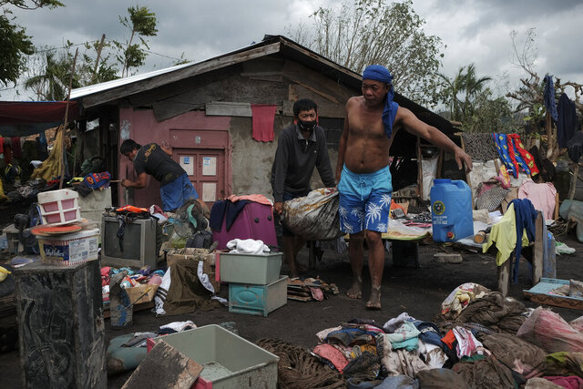 Residents try to save what's left of their belongings after heavy rains from Typhoon Goni washed down boulders and mudflows from Mayon Volcano, engulfing about 150 houses in a single community in the town of Guinobatan, Albay province, central Philippines on Monday, Nov. 2, 2020. More than a dozen of people were killed as Typhoon Goni lashed the Philippines over the weekend, and about 13,000 shanties and houses were damaged or swept away in the eastern island province that was first hit by the ferocious storm, officials said Monday. (AP Photo/John Michael Magdasoc)