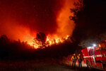 Firefighters watch the Bear Fire approach in Oroville, Calif., on Wednesday, Sept. 9, 2020. The blaze, part of the lightning-sparked North Complex, expanded at a critical rate of spread as winds buffeted the region.They work 50 hours at a stretch and sleep on gymnasium floors. Exploding trees shower them with embers. They lose track of time when the sun is blotted out by smoke, and they sometimes have to run for their lives from advancing flames. Firefighters trying to contain the massive wildfires in Oregon, California and Washington state are constantly on the verge of exhaustion as they try to save suburban houses, including some in their own neighborhoods. (AP Photo/Noah Berger)