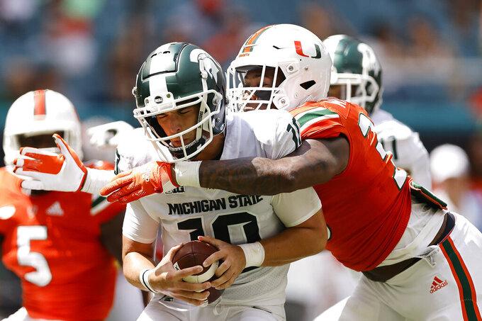 Miami defensive lineman Chantz Williams (33) sacks Michigan State quarterback Payton Thorne (10) during the first quarter of an NCAA college football game, Saturday, Sept. 18, 2021, in Miami Gardens, Fla. (AP Photo/Michael Reaves)