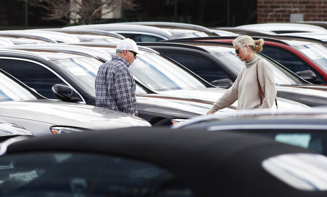 In this April 5, 2020, photo, a couple considers a sedan in a long row of 2020 models on display at a Mercedes Benz dealership in Littleton, Colo. Long-term auto loans allow people to spend more on a car while keeping the payments low. But issues down the road can prove costly. (AP Photo/David Zalubowski)