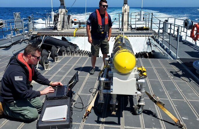 In this handout image from the U.S. Navy, sailors prepare a CARINA unmanned undersea drone off San Diego, California, April 19, 2021. The U.S. Navy's Mideast-based 5th Fleet said Wednesday, Sept. 8, 2021, it will launch a new task force that incorporates airborne, sailing and underwater drones after years of maritime attacks linked to ongoing tensions with Iran. (U.S. Navy/Lt. Cmdr. Tony Wright, via AP)