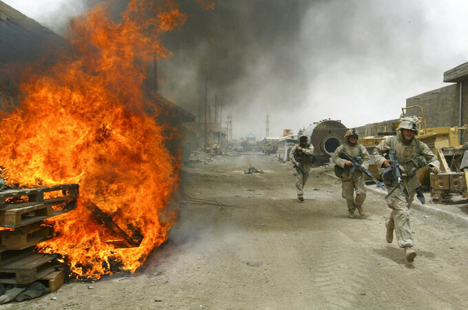 FILE - In this April 30, 2004, file photo, U.S. Marines burn their fortifications on front line positions in Fallujah, Iraq, before pulling out of the city. The U.S. launched its invasion of Iraq on March 20, 2003, unleashing a war that led to an insurgency, sectarian violence and tens of thousands of deaths. (AP Photo/John Moore, File)