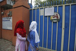 Pakistani students read a school closing notice at a gate of their school in Lahore, Pakistan, Thursday, Nov. 7, 2019. The government ordered all schools in the eastern Punjab capital of Lahore closed because of the poor air quality. A thick smog hung over the city of 11 million people on Thursday. (AP Photo/K.M. Chaudary)
