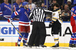 Linesman Scott Cherrey (50) separates New York Rangers defenseman Ryan Lindgren (55) and Boston Bruins left wing Brad Marchand (63) during a fight in the second period of an NHL hockey game Sunday, Feb. 16, 2020, at Madison Square Garden in New York. (AP Photo/Mary Altaffer