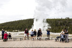 FILE - In this May 18, 2020 photo, visitors watch as Old Faithful erupts on the day the park partially reopened after a two-month shutdown due to the coronavirus pandemic, at Yellowstone National Park, Wyo. Lawmakers have reached bipartisan agreement on an election-year deal to double spending on a popular conservation program and devote nearly $2 billion a year to improve and maintain national parks. (Ryan Dorgan/Jackson Hole News & Guide via AP, File)
