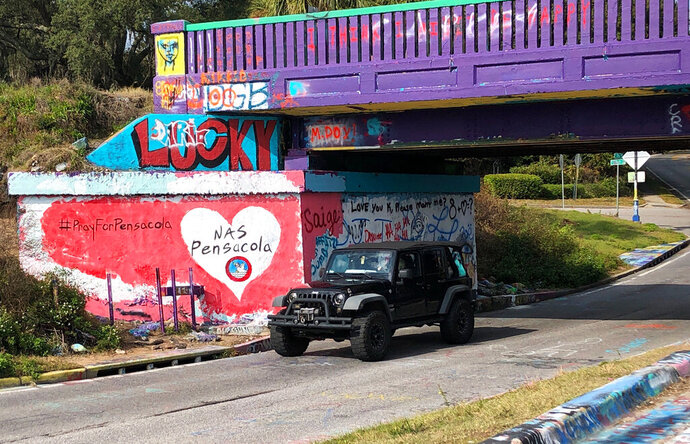 A vehicle drives by a tribute to victims of the Naval Air Station Pensacola that was freshly painted on what's known as Graffiti Bridge in downtown Pensacola, Fla., on Saturday, Dec. 7, 2019.  A US official says the Saudi student who fatally shot three people at the Florida naval base had hosted a dinner party earlier in the week to watch videos of mass shootings. The official spoke on condition of anonymity after being briefed by federal investigators. The official says a second Saudi student was recording outside the building at the Naval Air Station Pensacola on Friday while the shooting was happening inside. The official also says 10 Saudi students are being held at the base and that several others are unaccounted for.    (AP Photo/Brendan Farrington)