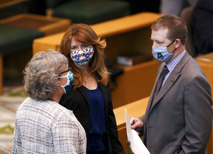 In this Wednesday, June 23, 2021, photo, Rep. Barbara Smith Warner, left, Rep. Christine Drazan and Rep. Duane Stark meet on the floor of the House of Representatives during the legislative session at the Oregon State Capitol in Salem., Ore. (Abigail Dollins/Statesman-Journal via AP)