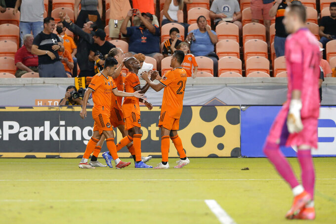 Houston Dynamo's Fafa Picault, center, is surrounded after his second goal of the game by team mates, from left, Memo Rodriguez, Griffin Dorsey and Darwin Ceren as Austin FC goalkeeper Brad Stuver, right, heads back into the goal during the second half of an MLS soccer match Saturday, Sept. 11, 2021, in Houston. (AP Photo/Michael Wyke)