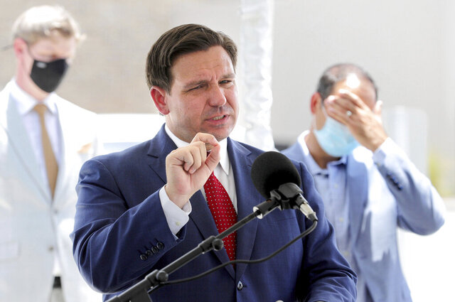 Florida Gov. Ron DeSantis gives an update on the state's response to the coronavirus pandemic during a press conference at Florida's Turnpike Turkey Lake Service Plaza, in Orlando, Friday, July 10, 2020. DeSantis made the visit to announce an increase in electric vehicle charging stations that will be available at turnpike plazas by year's end. (Joe Burbank/Orlando Sentinel via AP)