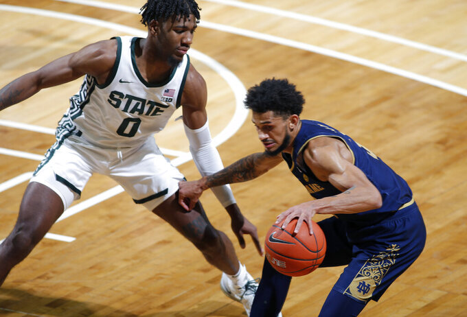 Notre Dame's Prentiss Hubb, right, drives against Michigan State's Aaron Henry during the first half of an NCAA college basketball game Saturday, Nov. 28, 2020, in East Lansing, Mich. Michigan State won 80-70. (AP Photo/Al Goldis)