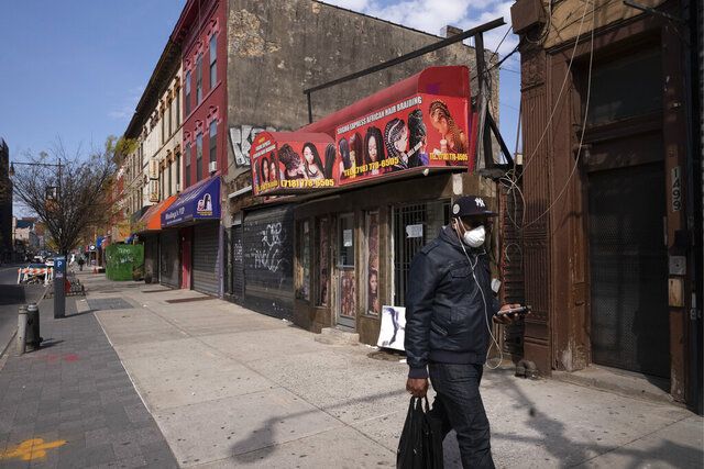 A man wearing a mask walks past Sogho Express African Hair Braiding salon, which is closed due to the coronavirus pandemic, Tuesday, April 7, 2020 in the Bedford Stuyvesant neighborhood of New York. Black-owned businesses have been almost twice as likely to fail as businesses overall during the current pandemic. That's according to a study released Tuesday, Aug. 4, 2020 by the Federal Reserve Bank of New York. (AP Photo/Mark Lennihan)