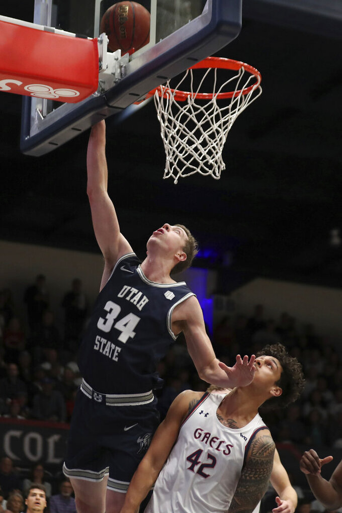 Utah State forward Justin Bean (34) shoots over Saint Mary's forward Dan Fotu (42) during the first half of an NCAA college basketball game in Moraga, Calif., Friday, Nov. 29, 2019. (AP Photo/Jed Jacobsohn)
