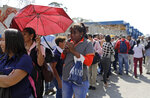 People line up at a bus stop during a power outage that suspended the subway service in Caracas, Venezuela, Monday, March 25, 2019. (AP Photo/Natacha Pisarenko)