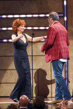 Reba McEntire, left, accepts the Artist of a Lifetime award from Vince Gill at 2019 CMT Artists of the Year at Schermerhorn Symphony Center on Wednesday, Oct. 16, 2019, in Nashville, Tenn. (Photo by Al Wagner/Invision/AP)