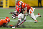 Georgia running back James Cook is tackled by Clemson linebacker James Skalski (47) and safety Andrew Mukuba during an NCAA college football game Saturday, Sept. 4, 2021, in Charlotte, N.C. (AP Photo/Chris Carlson)