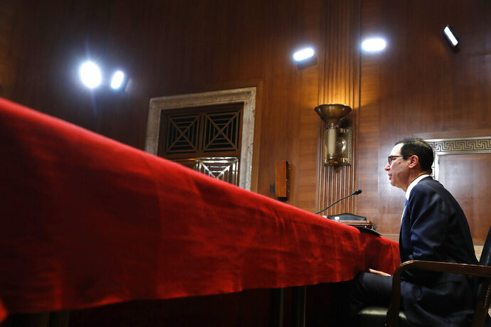 FILE- In this May 15, 2019, file photo Treasury Secretary Steve Mnuchin testifies about the budget during a Financial Services and General Government subcommittee hearing on Capitol Hill in Washington. In a letter Friday, July 12, to House and Senate leaders, Mnuchin told congressional leaders that Congress should raise the debt ceiling before leaving for its August recess. He says he could run out of maneuvering room to avoid an unprecedented default on the national debt before lawmakers return. (AP Photo/Jacquelyn Martin, File)