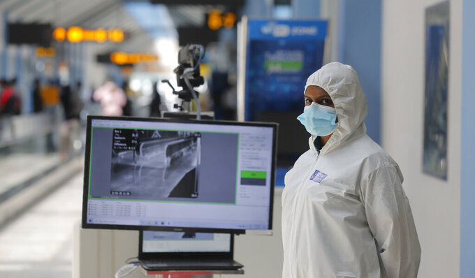 A Sri Lankan airport worker stands next to a thermal scanner inside a terminal at the Katunayake International Airport in Colombo, Sri Lanka, Wednesday, Jan. 20, 2021. Sri Lanka's tourism minister said that the airports in the country will be reopened for tourists according to health guidelines from Jan.21. (AP Photo/Eranga Jayawardena)
