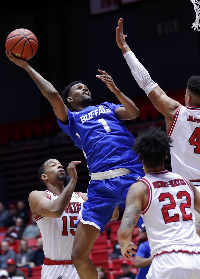 Buffalo forward Montell McRae (1) shoots against Northern Illinois forward Jaylen Key (15), forward Lacey James (4) and guard Rod Henry-Hayes (22) during the first half of an NCAA college basketball game Tuesday, Jan. 22, 2019, in DeKalb, Ill. (AP Photo/Nam Y. Huh)