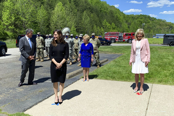 First lady Jill Biden, right, arrives at a vaccination clinic Thursday, May 13, 2021, at Capital High School in Charleston, W.Va. Arriving with her are actress Jennifer Garner, center, along with U.S. Sen. Joe Manchin, left, and his wife, Gayle Manchin. . (Kenny Kemp/Charleston Gazette-Mail via AP)