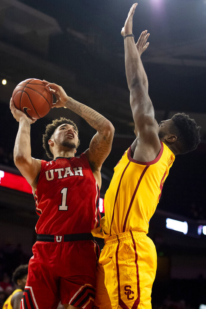 Utah forward Timmy Allen, left, shoots as Southern California guard Daniel Utomi defends during the second half of an NCAA college basketball game Thursday, Jan. 30, 2020 in Los Angeles. (AP Photo/Kyusung Gong)