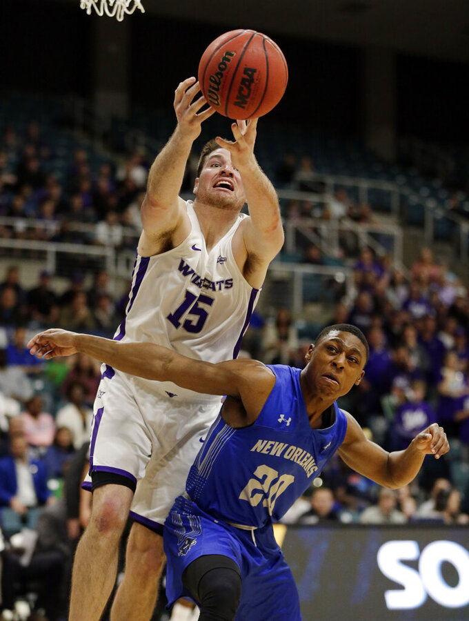 Abilene Christian forward Hayden Farquhar (15) reaches for a rebound over New Orleans guard Larry Robinson III (20) during the first half of an NCAA college basketball game for the Southland Conference men's tournament title Saturday, March 16, 2019, in Katy, Texas. (AP Photo/Michael Wyke)