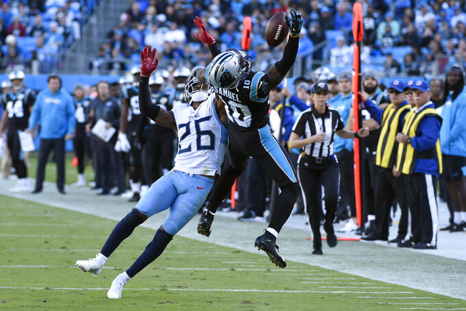 Tennessee Titans cornerback Logan Ryan (26) and Carolina Panthers wide receiver Curtis Samuel (10) reach for a pass during the second half of an NFL football game in Charlotte, N.C., Sunday, Nov. 3, 2019. The pass was incomplete. (AP Photo/Mike McCarn)