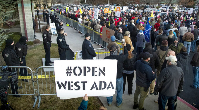 Boise police were forced to create a barrier to keep anti-mask protesters from entering a meeting at the Central District Health offices, Tuesday, Dec. 8, 2020 in Boise, Idaho. The special meeting of the CDH board was later cancelled.  (Darin Oswald/Idaho Statesman via AP)