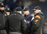 New York Yankees manager Aaron Boone, second from right, and Baltimore Orioles manager Brandon Hyde, right, discuss wet field conditions before a baseball game Monday, May 13, 2019, in New York. The game was postponed due to unplayable field conditions. The teams will play a doubleheader on Wednesday. (AP Photo/Kathy Willens)