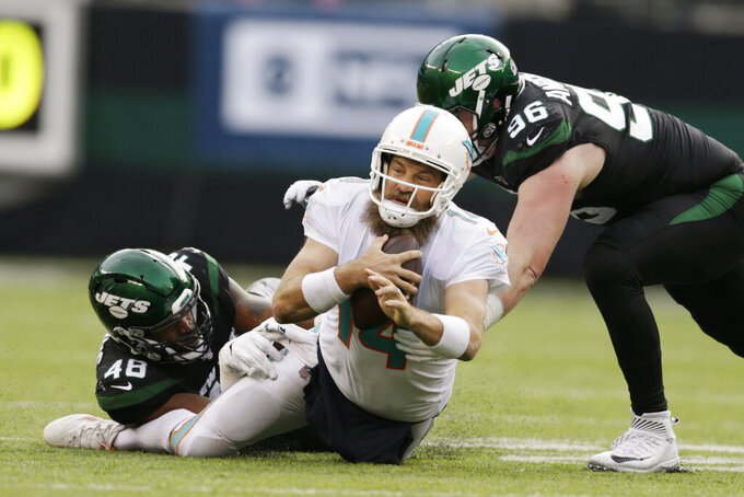 Miami Dolphins quarterback Ryan Fitzpatrick (14) is stopped by New York Jets defensive end Henry Anderson (96) and New York Jets outside linebacker Jordan Jenkins (48) during the second half of an NFL football game, Sunday, Dec. 8, 2019, in East Rutherford, N.J. (AP Photo/Adam Hunger)