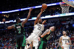 New Orleans Pelicans center Derrick Favors (22) is fouled as he goes to the basket between Boston Celtics guard Jaylen Brown (7) and center Daniel Theis in the first half of an NBA basketball game in New Orleans, Sunday, Jan. 26, 2020. (AP Photo/Gerald Herbert)