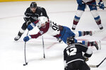 Colorado Avalanche right wing Mikko Rantanen, center, shoots over a reach by Los Angeles Kings defenseman Matt Roy, top, during the second period of an NHL hockey game Tuesday, Jan. 19, 2021 in Los Angeles. (AP Photo/Kyusung Gong)