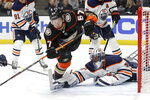 Anaheim Ducks left wing Rickard Rakell trips over Edmonton Oilers goaltender Mike Smith during the second period of an NHL hockey game in Anaheim, Calif., Tuesday, Feb. 25, 2020. (AP Photo/Chris Carlson)