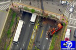 In this image taken from video provided by WABC-TV, first responders work the scene after a garbage truck careened off an overpass onto the westbound lanes of Route 495, Thursday, July 3, 2019, in Union City, N.J. (WABC-TV via AP)