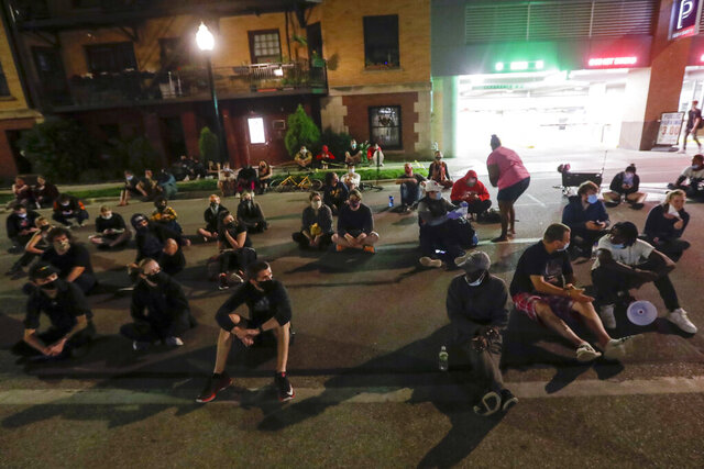 Protesters sit on the street outside the Dane County Jail on Wednesday, June 24, 2020, in Madison, Wis. About 40 people gathered outside the jail, calling for the release of a Black man who was arrested Tuesday after shouting at restaurant customers through a megaphone while carrying a baseball bat. (AP Photo/Morry Gash)