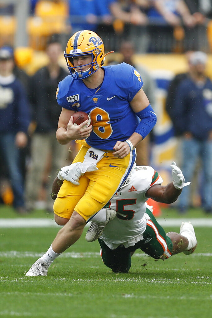 Pittsburgh quarterback Kenny Pickett (8) scrambles for a first down past Miami defensive lineman Gregory Rousseau (15) during the first half of an NCAA college football game, Saturday, Oct. 26, 2019, in Pittsburgh. (AP Photo/Keith Srakocic)