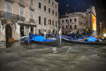 Stranded gondolas float adrift over the flooded banks, in Venice, Wednesday, Nov. 13, 2019. The mayor of Venice is blaming climate change for flooding in the historic canal city that has reached the second-highest levels ever recorded, as another exceptional water level was recorded Wednesday. (AP Photo/Luigi Costantini)