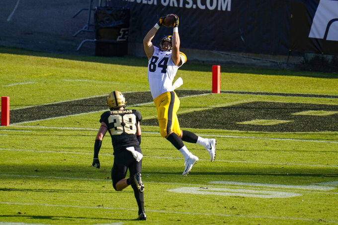 Iowa tight end Sam LaPorta (84) makes a catch in front of Purdue defensive tackle Anthony Watts (8) during the second quarter of an NCAA college football game in West Lafayette, Ind., Saturday, Oct. 24, 2020. (AP Photo/Michael Conroy)