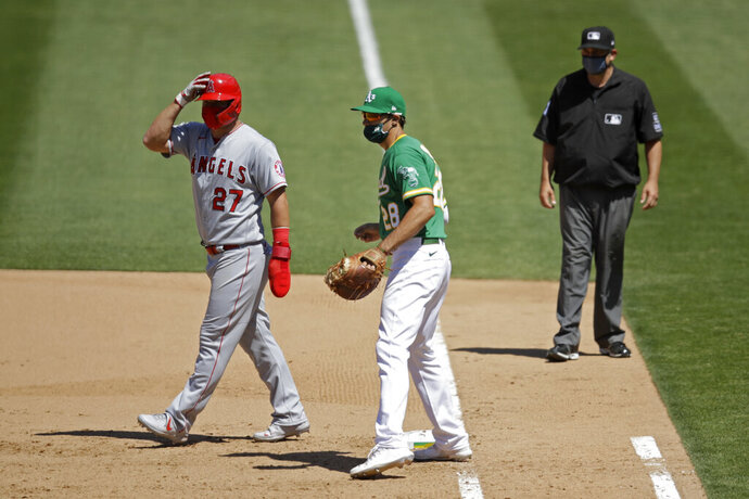 FILE  - In this Monday, July 27, 2020, file photo, Oakland Athletics' Matt Olson (28) wears a mask as Los Angeles Angels' Mike Trout, left, also wears one while taking a lead off first base during the eighth inning of a baseball game in Oakland, Calif. Baseball's Western Divisions have so far avoided any COVID-related schedule disruptions and they're trying to keep it that way. (AP Photo/Ben Margot, File)