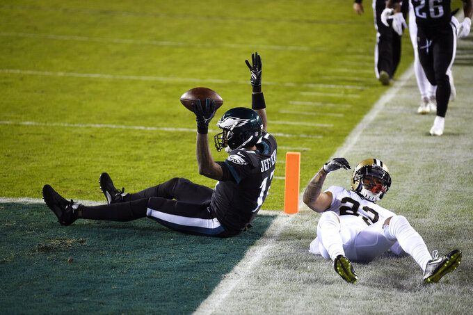 Philadelphia Eagles' Alshon Jeffery, left, reacts after scoring a touchdown against New Orleans Saints' Marshon Lattimore during the first half of an NFL football game, Sunday, Dec. 13, 2020, in Philadelphia. (AP Photo/Derik Hamilton)