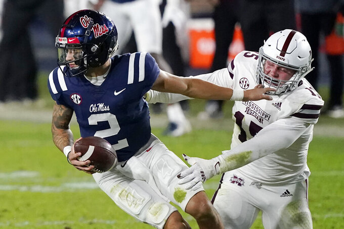 Mississippi quarterback Matt Corral (2) evades a sack by Mississippi State defensive end Jack Harris (15) during the second half of an NCAA college football game, Saturday, Nov. 28, 2020, in Oxford, Miss. Mississippi won 31-24. (AP Photo/Rogelio V. Solis)