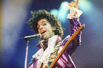 FILE - In this Feb. 18, 1985 file photo, Prince performs at the Forum in Inglewood, Calif. The music icon died of an accidental opioid overdose at his Paisley Park studio on April 21, 2016. He was 57.  (AP Photo/Liu Heung Shing, File)