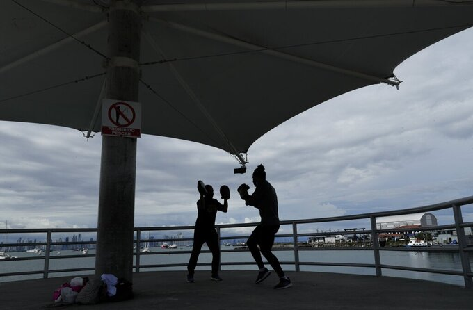 Cuban boxer Yunier Menen, right, and his trainer Carlos Agrazal train at the Amador causeway amid the COVID-19 pandemic in Panama City, Monday, Sept. 14, 2020. Panama lifted a months-old coronavirus measure on Monday that restricted women to going out one day, and men the next. (AP Photo/Arnulfo Franco)