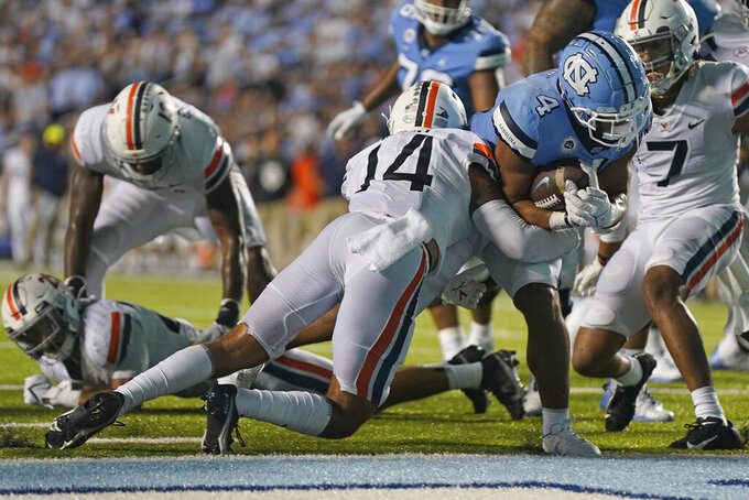 North Carolina running back Caleb Hood (4) scores a touchdown as Virginia defensive back Antonio Clary (14) tries to tackle him during the second half of an NCAA college football game in Chapel Hill, N.C., Saturday, Sept. 18, 2021. (AP Photo/Gerry Broome)