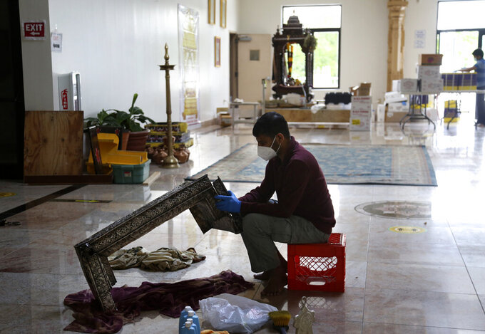 Shravan Chinnala cleans the Peetam, a silver pedestal for the image of the Hindu goddess Lakshmi, in preparation for Maha Kumbhabhishekam, a five-day rededication ceremony at the Sri Venkateswara Temple in Penn Hills, Pa., Tuesday, June 22, 2021. Built in the 1970s, the Sri Venkateswara Temple is the oldest major Hindu temple in the country. Maha Kumbhabhishekams occur about every 12 years and involve ceremonies to reenergize the temple and its deities. (AP Photo/Jessie Wardarski)