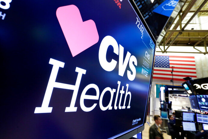 FILE- In this Dec. 4, 2017, file photo, the CVS Health logo appears above a trading post on the floor of the New York Stock Exchange.  CVS Health's second-quarter performance beat Wall Street's expectations as the drugstore chain and pharmacy benefits manager experienced reduced benefit costs. It raised its full-year earnings forecast. (AP Photo/Richard Drew, File)